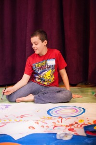 A Firefly Arts participant designing his next mandala for a family  painting project. Photo credit: Stephanie Letzkus of Letzkus Photography